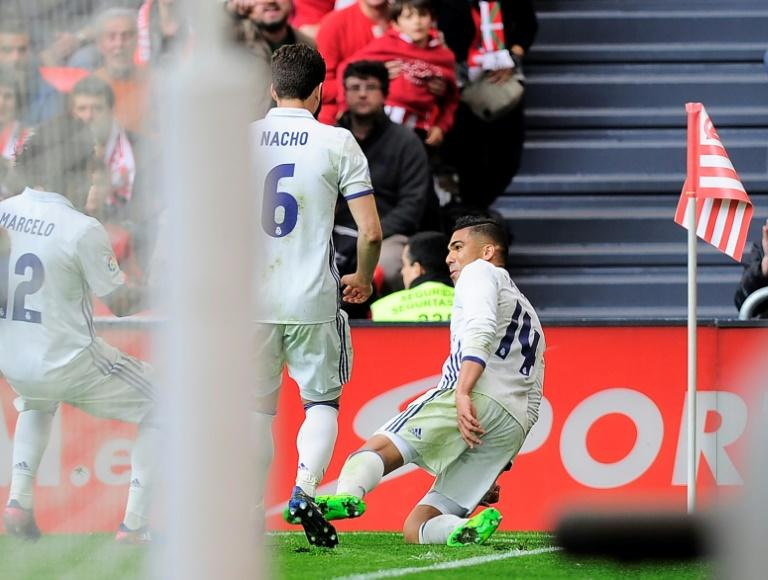 Real Madrid's midfielder Carlos Henrique Casemiro (R) celebrates after scoring his team's second goal during the Spanish league football match against Athletic Club Bilbao at the San Mames stadium in Bilbao on March 18, 2017