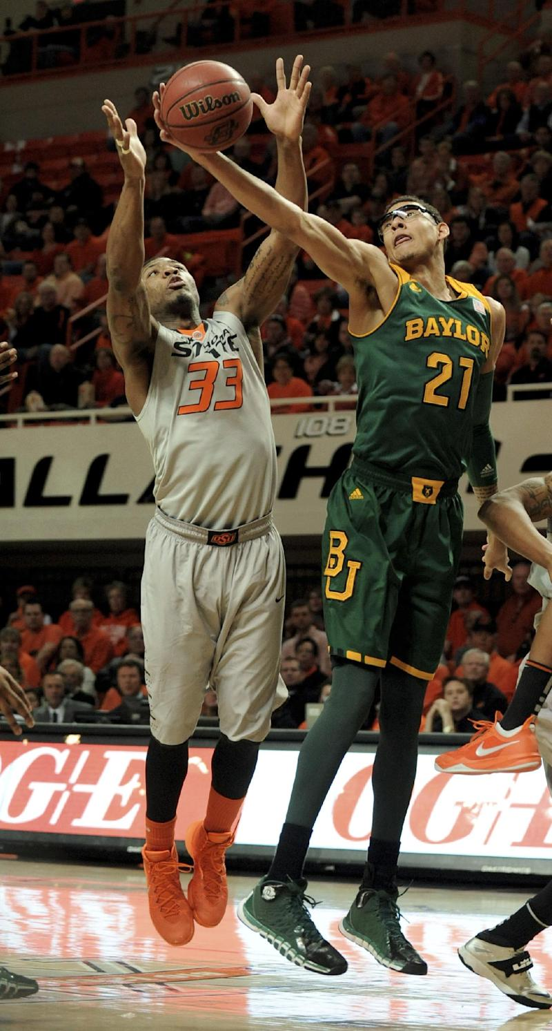 Baylor center Isaiah Austin (21) and Oklahoma State guard Marcus Smart reach for a rebound during the first half of an NCAA college basketball game in Stillwater, Okla., Saturday, Feb. 1, 2014. (AP Photo/Brody Schmidt)