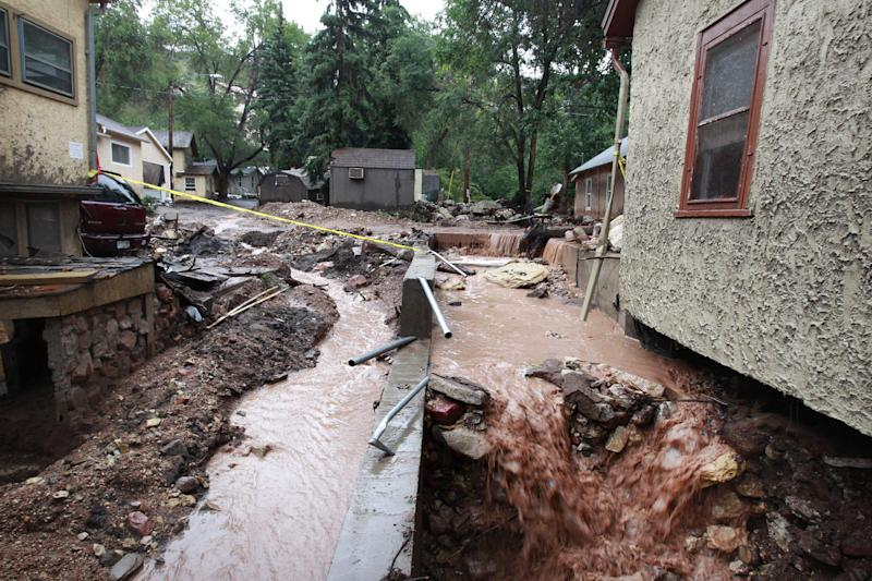 In this Aug. 13, 2013 photo, run off from a heavy rainstorm runs through the foundations of debris-strewn homes destroyed in a flash flood, in Manitou Springs, Colo. Manitou Springs lies downstream of the vast swaths of scorched earth left behind by last year's Waldo Canyon Fire, making the town highly prone to flash flooding. In Colorado, multiple flash floods have struck this summer in or near scars left by last year's wildfires. (AP Photo/Brennan Linsley)
