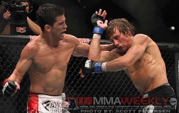 Dominick Cruz [L] punches rival Urijah Faber. (MMA Weekly)