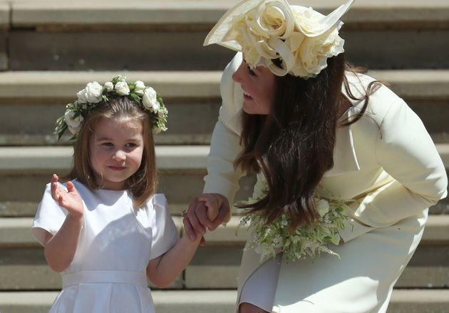 TOPSHOT - Princess Charlotte (L) waves by her mother Britain's Catherine, Duchess of Cambridge after attending the wedding ceremony of Britain's Prince Harry, Duke of Sussex and US actress Meghan Markle at St George's Chapel, Windsor Castle, in Windsor, on May 19, 2018. (Photo by Jane Barlow / POOL / AFP) (Photo credit should read JANE BARLOW/AFP via Getty Images)
