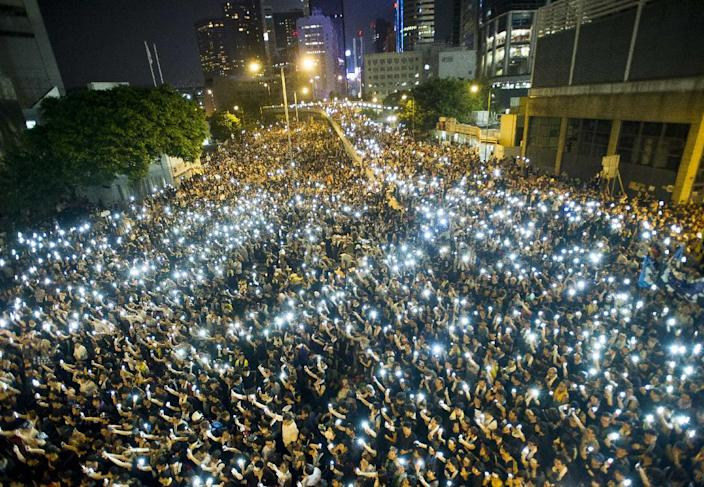 Pro-democracy activists hold up their mobile phones during protests in Hong Kong following China's refusal to grant citizens full universal suffrage (AFP Photo/Xaume Olleros)
