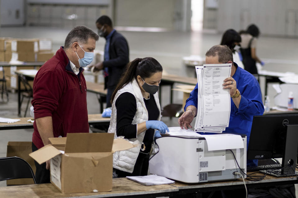 Workers scan ballots as the Fulton County presidential recount gets under way Wednesday morning, Nov. 25, 2020 at the Georgia World Congress Center in Atlanta.  (Ben Gray/AP)