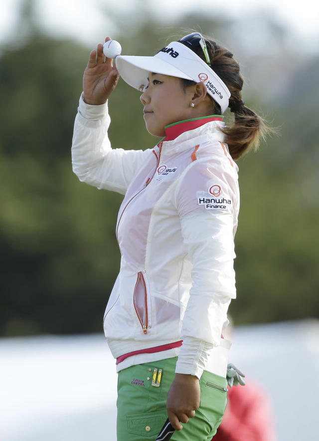 Jenny Shin holds up her ball on the 18th green of the Lake Merced Golf Club after finishing the third round of the Swinging Skirts LPGA Classic golf tournament on Saturday, April 26, 2014, in Daly City, Calif. (AP Photo/Eric Risberg)