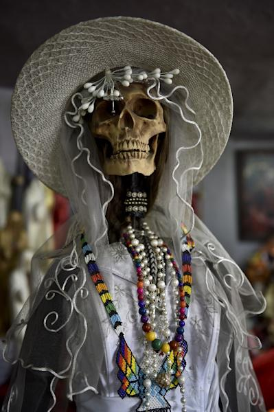 View of a figure of the Santa Muerte (Holy Death) dressed as a bride at a sanctuary in Santa Maria Cuautepec, Tultitlan, Mexico on February 7, 2016 (AFP Photo/Yuri Cortez)