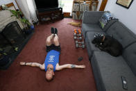 Christian Hainds stretches after his workout session as his dog, Reyna and cat, Oscar, lounge at his home in Hammond, Ind., Monday, June 7, 2021. Health officials have warned since early on in the pandemic that obesity and related conditions such as diabetes were risk factors for severe COVID-19. It wasn't until he was diagnosed as diabetic around the start of the pandemic that he felt the urgency to make changes. Hainds lost about 50 pounds during the pandemic, and at 180 pounds and 5 feet, 11 inches tall is no longer considered obese. (AP Photo/Shafkat Anowar)
