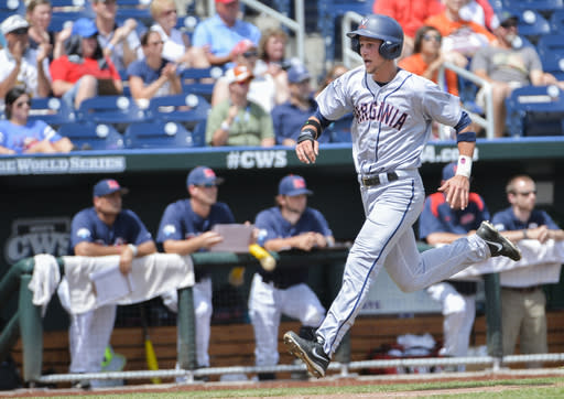 Virginia's Brandon Downes runs past the Mississippi dugout on his way to score on a two-run single hit by Robbie Coman in the fourth inning of an NCAA baseball College World Series game in Omaha, Neb., Saturday, June 21, 2014. (AP Photo/Ted Kirk)