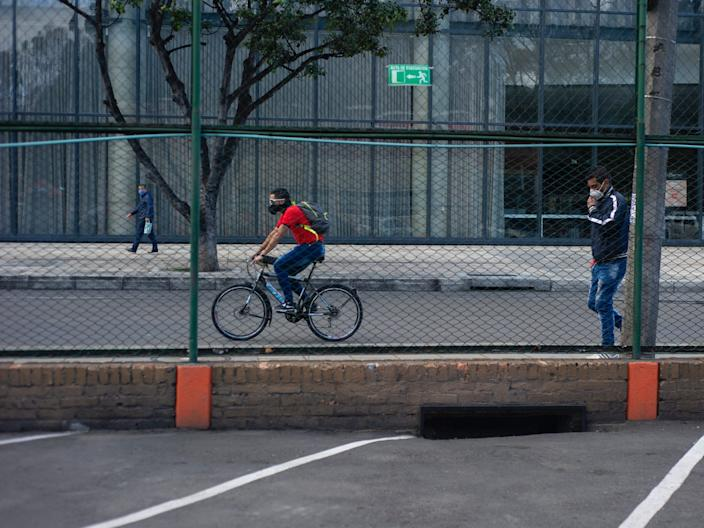 """Two men one on a bike and the other walking use protective face masks on August 1 2020 in Bogota, Colombia. <p class=""""copyright"""">Sebastian Barros/NurPhoto via Getty Images</p>"""