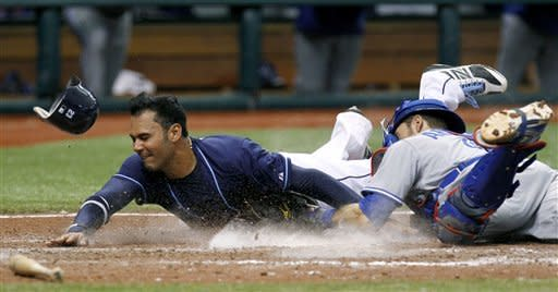 Tampa Bay Rays' Carlos Pena, left, is tagged out at home plate by Toronto Blue Jays catcher J.P. Arencibia during the ninth inning of a baseball game, Wednesday, May 23, 2012, in St. Petersburg, Fla. Pena tried to score from second base on an ground ball by Drew Sutton. (AP Photo/Chris O'Meara)