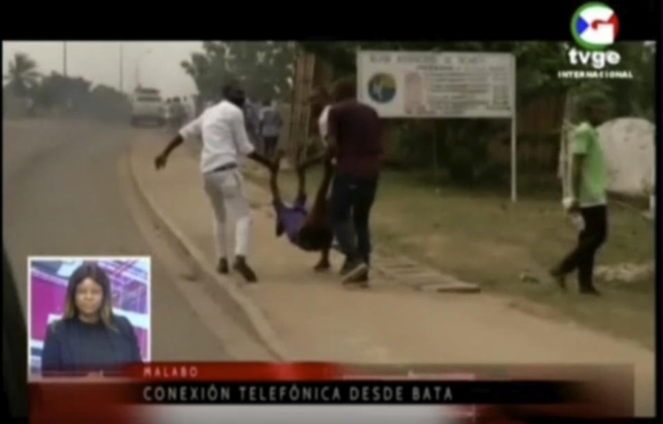 This TVGE image made from video shows people carrying a victim away after a blast site at a military barracks in Bata, Equatorial Guinea, Sunday, March 7, 2021. A series of explosions killed at least 20 people and wounded more than 600 others on Sunday, authorities said. (TVGE via AP)