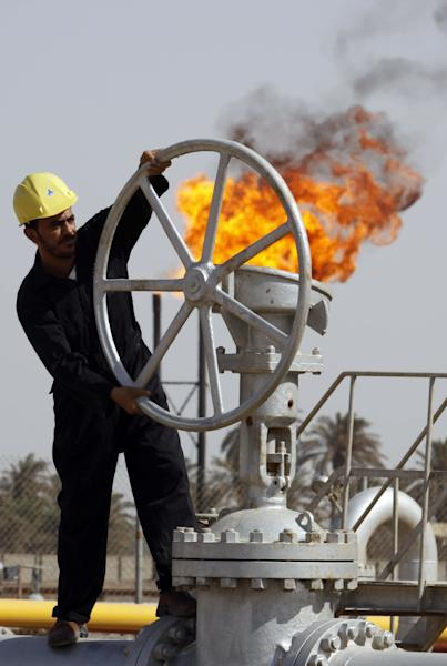 FILE - In this file photo of Friday, July 17, 2009, an Iraqi worker operates valves at the Nahran Omar oil refinery near the city of Basra, 340 miles (550 kilometers) southeast of Baghdad, Iraq. Iraq's oil ministry said Thursday April 19, 2012 that the U.S. oil giant Exxon Mobil Corp. is not allowed to bid in the May energy auction because of its oil deals with the northern self-ruled Kurdish region in Iraq. (AP Photo/Nabil al-Jourani, File)