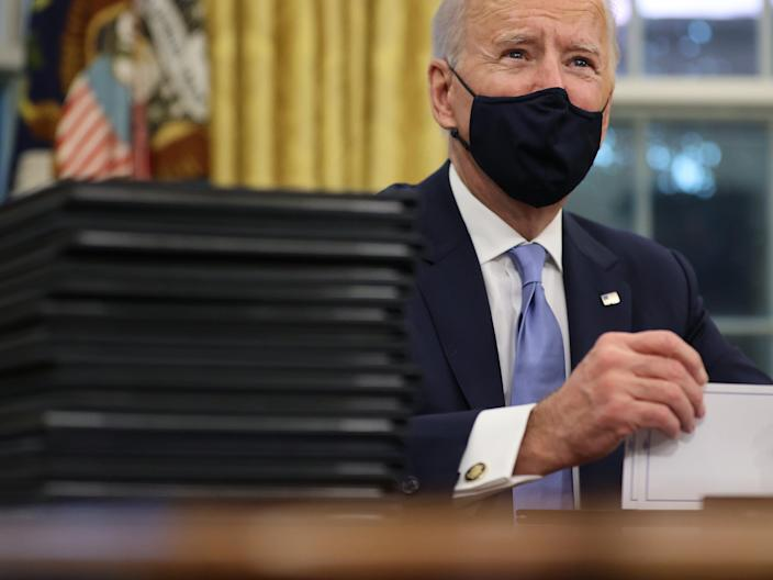 <p>US President Joe Biden prepares to sign a series of executive orders at the Resolute Desk in the Oval Office just hours after his inauguration on 20 January, 2021</p> (Getty Images)