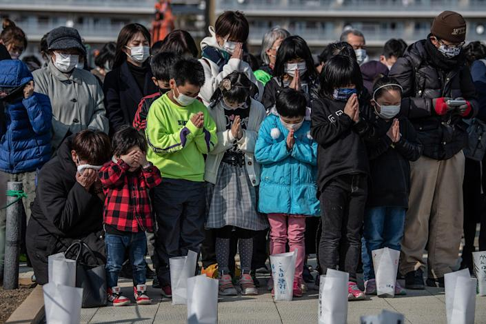 Image: A woman and child cover their eyes as others pray during a minute of silence to mark the 10th anniversary of the 2011 Tohoku earthquake and tsunami (Carl Court / Getty Images)