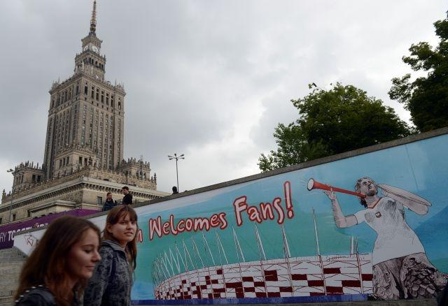 Two women walk by the Euro 2012 football fanzone near the Palace of Culture in the center of Poland's capital Warsaw