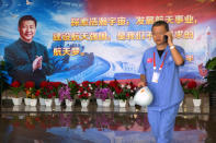 A worker walks past a billboard with a quotation from Chinese President Xi Jinping in a building at the Wenchang Space Launch Site in Wenchang in southern China's Hainan province, Monday, Nov. 23, 2020. Chinese technicians were making final preparations Monday for a mission to bring back material from the moon's surface for the first time in nearly half a century — an undertaking that could boost human understanding of the moon and of the solar system more generally. (AP Photo/Mark Schiefelbein)