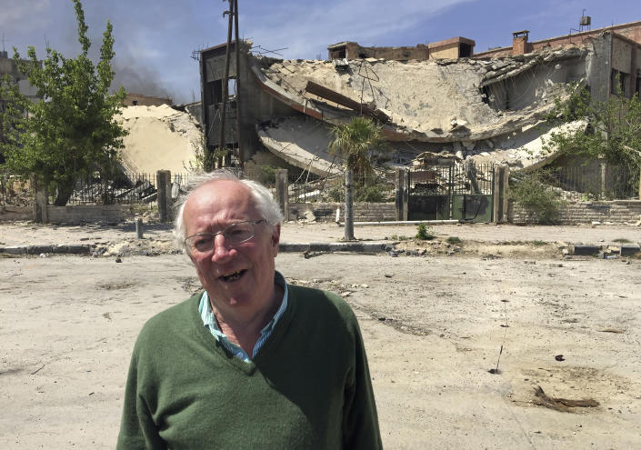 Veteran British journalist Robert Fisk stands in front of a damaged building in the Damascus suburb of Douma, during a tour by Syria's Information Ministry to the town days after it was captured from rebels by Syrian government forces, April 16, 2018. Fisk, one of the best-known Middle East correspondents who spent his entire career reporting from the troubled region and won accolades for challenging mainstream narratives died Sunday at a hospital in Dublin after a short illness. He was 74. (AP Photo/Bassem Mroue)