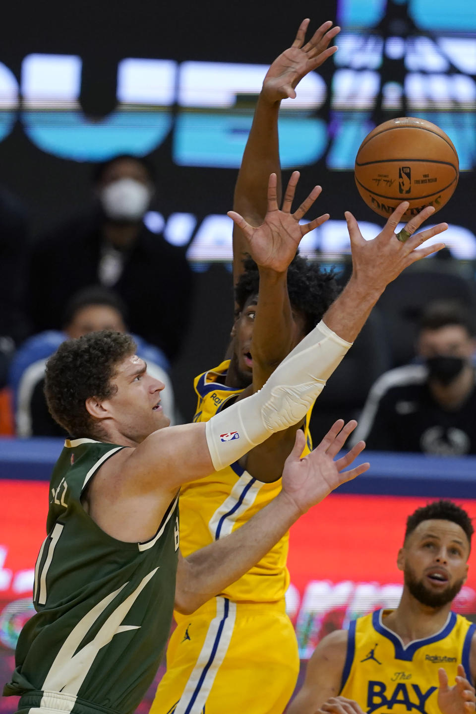 Milwaukee Bucks center Brook Lopez, left, shoots against Golden State Warriors center James Wiseman during the second half of an NBA basketball game in San Francisco, Tuesday, April 6, 2021. (AP Photo/Jeff Chiu)