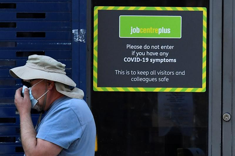A person wearing a protective face mask walks past a Job Centre Plus office, amidst the outbreak of the coronavirus disease (COVID-19) in London, Britain, August 11, 2020. REUTERS/Toby Melville
