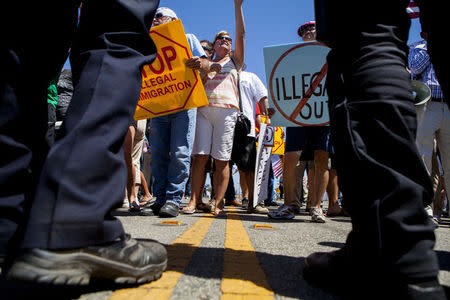 Law enforcement attempt to control demonstrators in Murrieta, California July 1, 2014. REUTERS/Sam Hodgson