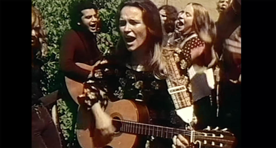 Woman sings and plays guitar on street, surrounded by other cult members. Source: Children of God/ YouTube
