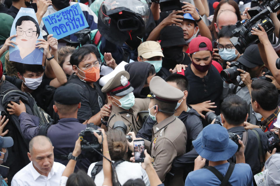 Police officials scuffle with pro-democracy demonstrators during an anti-government protest at Victory Monument in Bangkok, Thailand, Sunday, Oct. 18, 2020. Thai police on Sunday declined to say whether they were taking a softer approach toward student anti-government demonstrations, after several mass rallies attracting thousands of protesters ended peacefully in Bangkok on Saturday. (AP Photo/Sakchai Lalit)