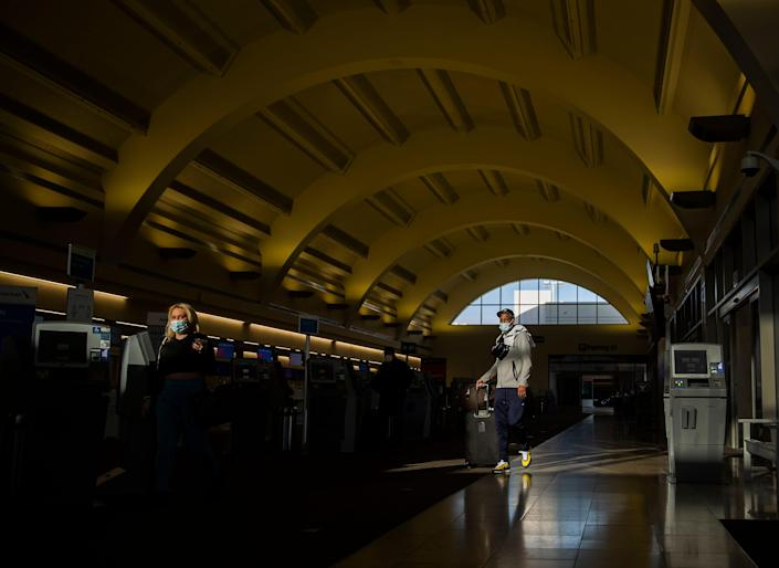 A man in a mask stands under the curved terminal ceiling at John Wayne Airport in California