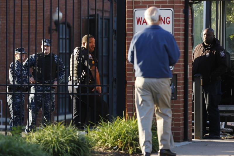 A Navy Yard personnel approaches a security checkpoint as he returns to work two days after a gunman killed 12 people, in Washington