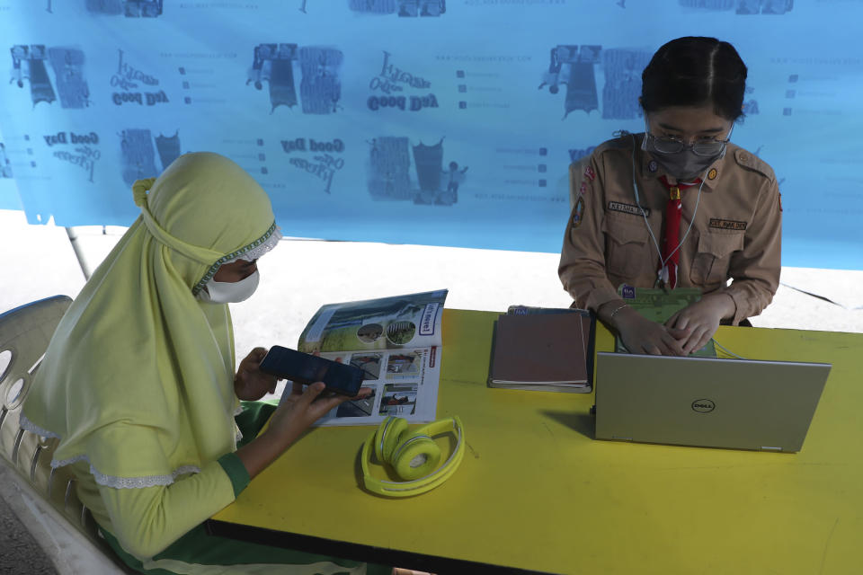 Students wear face masks to help curb the spread of the new coronavirus as they use free wifi to access an online lesson inside a temporary tent in Jakarta, Indonesia, Wednesday, Aug. 12, 2020. In some area of the country, students are still yet to go to school due to the coronavirus. (AP Photo/Achmad Ibrahim)