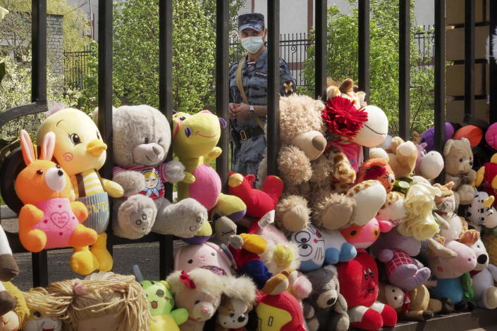 A Russian Rosguardia (National Guard) soldier stands guard at a school after a shooting on Tuesday in Kazan, Russia, Thursday, May 13, 2021, with toys brought by people in the foreground. Russian officials say a gunman attacked a school in the city of Kazan and Russian officials say several people have been killed. Officials said the dead in Tuesday's shooting include students, a teacher and a school worker. Authorities also say over 20 others have been hospitalised with wounds. (AP Photo/Dmitri Lovetsky)