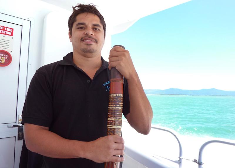 Aboriginal Australian Gavin Singleton stands with his digderidoo on a boat travelling to the Great Barrier Reef (AFP Photo/Glenda Kwek)