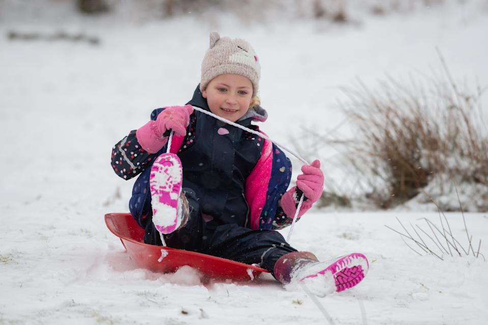A little girl is pulled along by a sled as the cold snap continues in Sevenoaks, Kent. (SWNS)