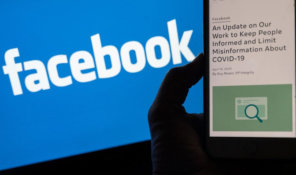 In this photo illustration, a smart phone screen displays a new policy on Covid-19 misinformation with a Facebook website in the background, on May 27, 2021, in Arlington, Virginia - Facebook has reversed its policy banning posts suggesting the Covid-19 was man-made, on the heels of renewed debate over the origins of the virus which first emerged in China. (Photo by ANDREW CABALLERO-REYNOLDS / AFP) (Photo by ANDREW CABALLERO-REYNOLDS/AFP via Getty Images)