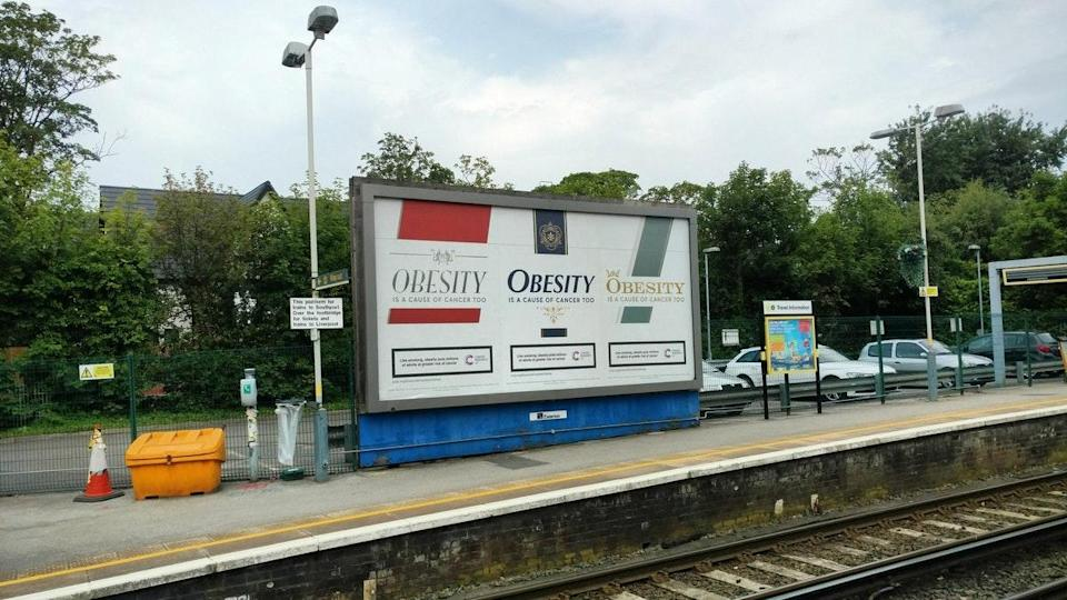 The new advert features a cigarette packet bearing the slogan 'obesity is a cause of cancer too'.