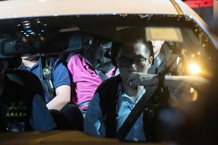 A man (pink shirt) is taken away by Hong Kong police, who said they arrested a total of six men including some with alleged triad backgrounds, after suspected gangsters attacked anti-government demonstrators in Yuen Long district (AFP Photo/Philip FONG)