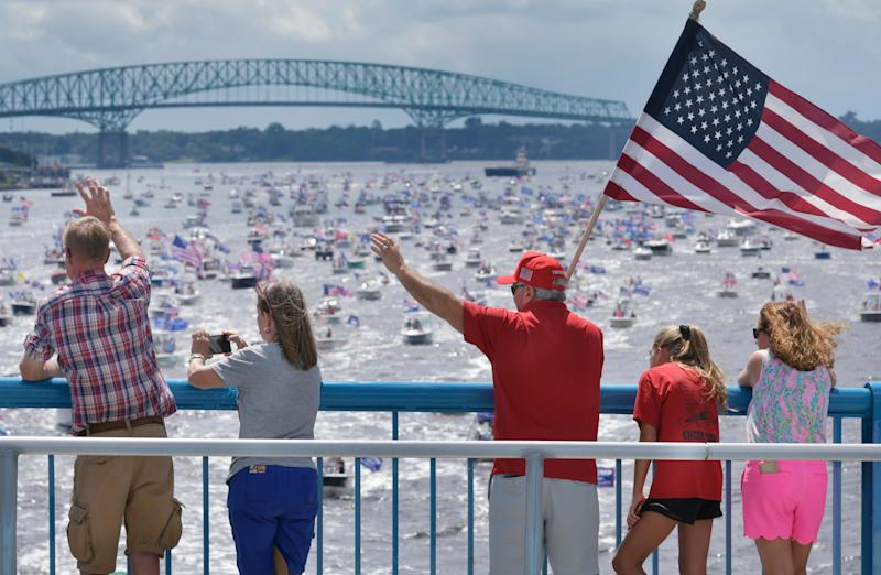 Supporters of President Donald Trump wave at the hundreds of boats idling on the St. Johns River during a rally Sunday, June 14, 2020, in Jacksonville, Fla., celebrating Trump's birthday.