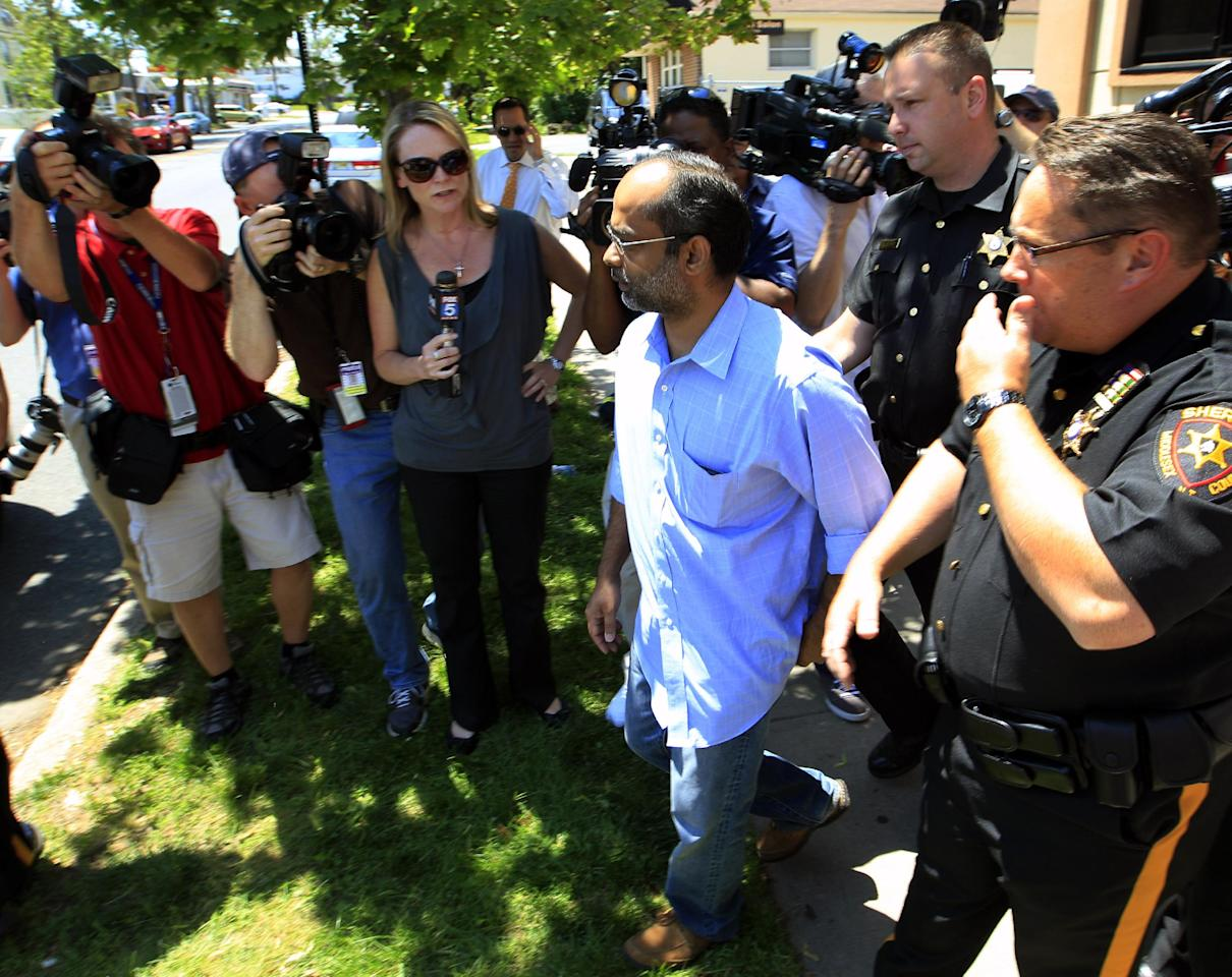 Ravi Pazhani, leaves the Middlesex County sheriff's department past officers and the media in New Brunswick, N.J., Thursday, May 31, 2012, after the arrival of his son, Dharun Ravi. The former Rutgers University student convicted of using a webcam to spy on his gay roommate was to report to the sheriff on his way to jail. Ravi, 22, arrived at the sheriff's department shortly after 12:30 p.m. to be fingerprinted and photographed before being driven to the county jail to serve a 30-day term. (AP Photo/Mel Evans)