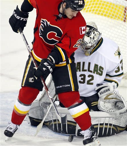 Dallas Stars goalie Kari Lehtonen, from Finland, right, and Calgary Flames' Mark Giordano battle for the puck during the first period of an NHL hockey game in Calgary, Alberta, Monday, March 26, 2012. (AP Photo/The Canadian Press, Jeff McIntosh)