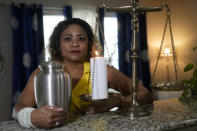 Daphne Bolton holds an urn containing the ashes of her brother at her home on Monday, May 31, 2021, in Charlotte, N.C. Bolton's brother, Johnny Lorenzo Bolton, a 49-year-old Black man was shot shoot to death by a Cobb County Sheriff's Office SWAT team member serving a search warrant last December. (AP Photo/Chris Carlson)