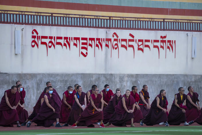 A class of monks do stretching exercises on an athletic field at the Tibetan Buddhist College near Lhasa in western China's Tibet Autonomous Region, as seen during a rare government-led tour of the region for foreign journalists, Monday, May 31, 2021. Long defined by its Buddhist culture, Tibet is facing a push for assimilation and political orthodoxy under China's ruling Communist Party. (AP Photo/Mark Schiefelbein)