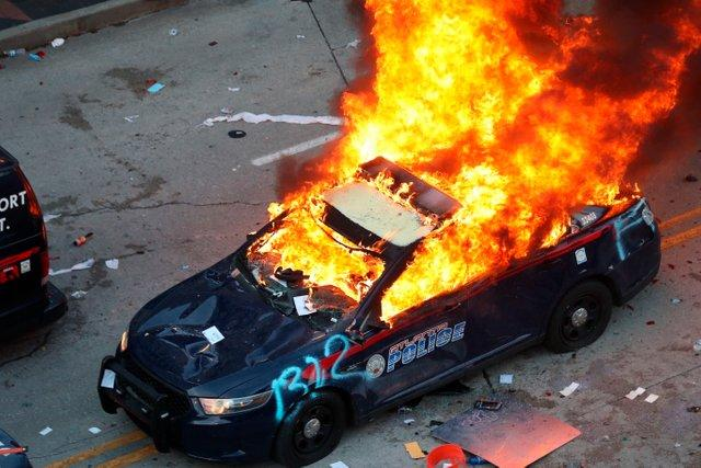 A police car burns after protesters marched to the Georgia State Capitol