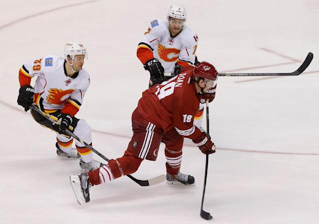 Calgary Flames' T.J. Galiardi (39) and T.J. Brodie (7) defends as Phoenix Coyotes' Shane Doan shoots on goal during the third period of NHL hockey game, Saturday, March 15, 2014, in Glendale, Ariz. The Coyotes won 3-2. (AP Photo/Matt York)