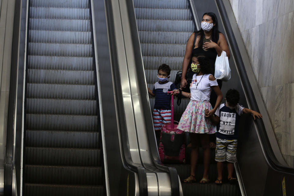 A family wears face masks at a bus station in Brasilia, Brazil, Monday, May 4, 2020. The state government mandated that people using public transportation must wear face masks starting Monday to help contain the spread of the new coronavirus. (AP Photo/Eraldo Peres)
