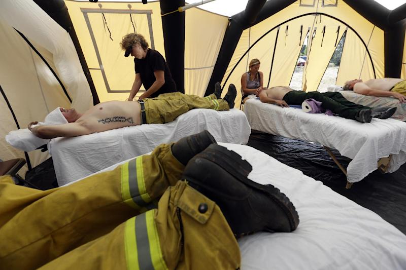 Several firefighters from Colorado Springs Fire Dept. get massages after coming off the fire line on the the Waldo Canyon wildfire west of Colorado Springs, Colo., Friday, June 29, 2012. One person has been found dead, another is missing and nearly 350 homes have been destroyed by a raging U.S. wildfire that has forced tens of thousands to flee this week. President Barack Obama on Friday will tour the scene of the most destructive fire in Colorado history. (AP Photo/Chris Carlson)