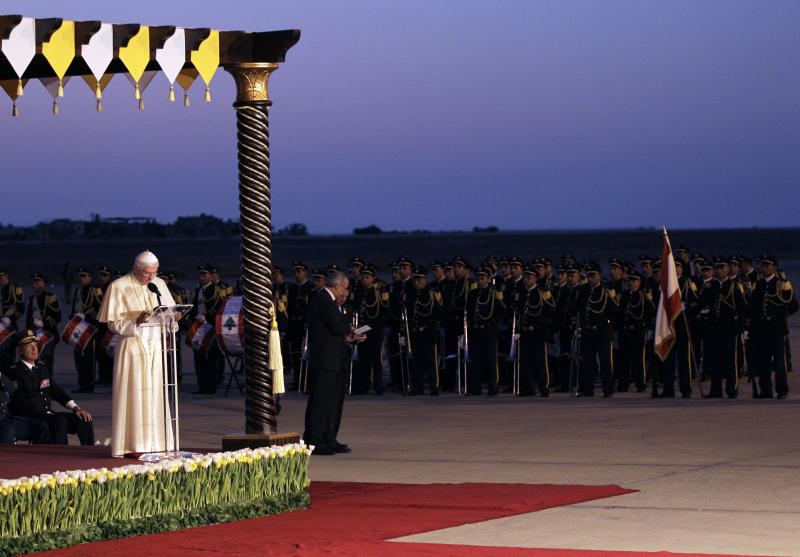 """Pope Benedict XVI, left, addresses a speech in front of Lebanese honor guards during his departure ceremony, at Rafik Hariri International airport, in Beirut, Lebanon, Sunday Sept. 16, 2012. Pope Benedict XVI end his three days visit to Lebanon after he celebrated an open-air mass for tens of thousands of pilgrims from across the Middle East, saying Christians must do their part to end the """"grim trail of death and destruction"""" in the region. (AP Photo/Hussein Malla)"""