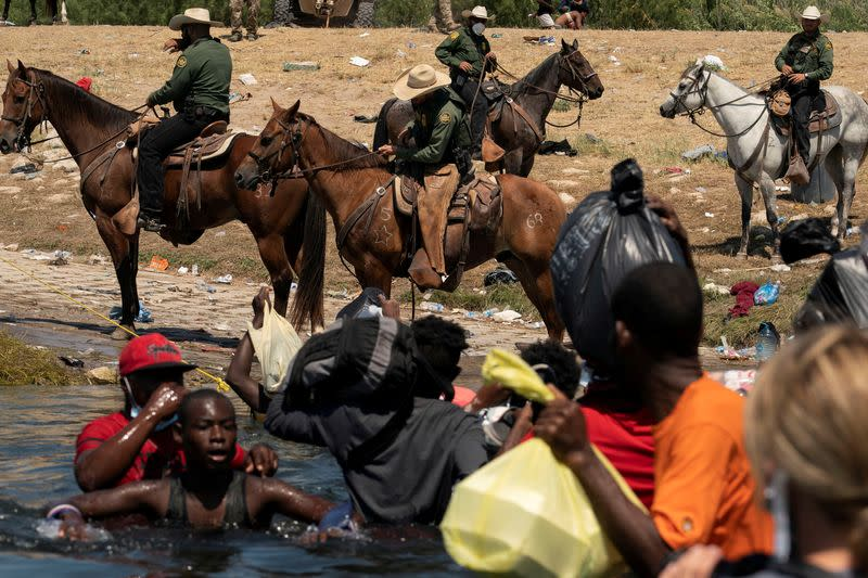 FILE PHOTO: Asylum-seeking migrants in the U.S. return to the Mexican side of the border, in Ciudad Acuna