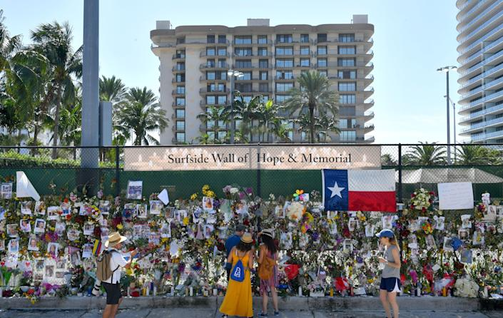 The Champlain Towers South condominium is visible behind the memorial wall for people missing in the collapse of the building in Surfside Florida. Recovery efforts were suspended Saturday afternoon while crews begin preparing the remaining structure for demolition.