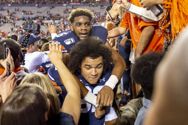 Auburn offensive lineman Kameron Stutts (62) gives defensive back Xavier McKinney (15) a ride off the crowded field after their upset of Alabama in an NCAA college football game, Saturday, Nov. 30, 2019, in Auburn, Ala. (AP Photo/Vasha Hunt)