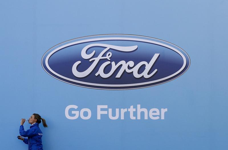 Woman walks past a logo of carmaker Ford at the entrance to a media event for the launch of a concept car in Sydney