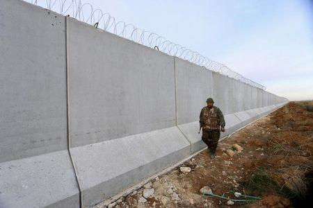 A Kurdish People's Protection Units (YPG) fighter walks near a wall, which activists said was put up by Turkish authorities, on the Syria-Turkish border in the western countryside of Ras al-Ain, Syria