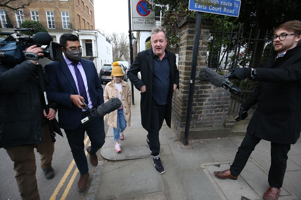 Piers Morgan (centre) speaks to reporters as he walks his daughter Elise to school in Kensington, central London, the morning after it was announced by broadcaster ITV that he was leaving as a host of Good Morning Britain. Picture date: Wednesday March 10, 2021.